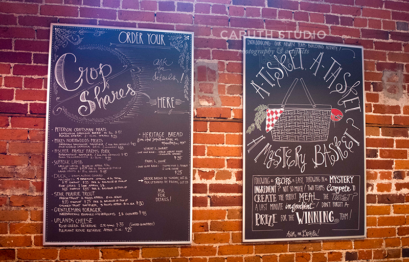 chalk boards hung on a brick wall with upcoming cooking classes and demonstrations