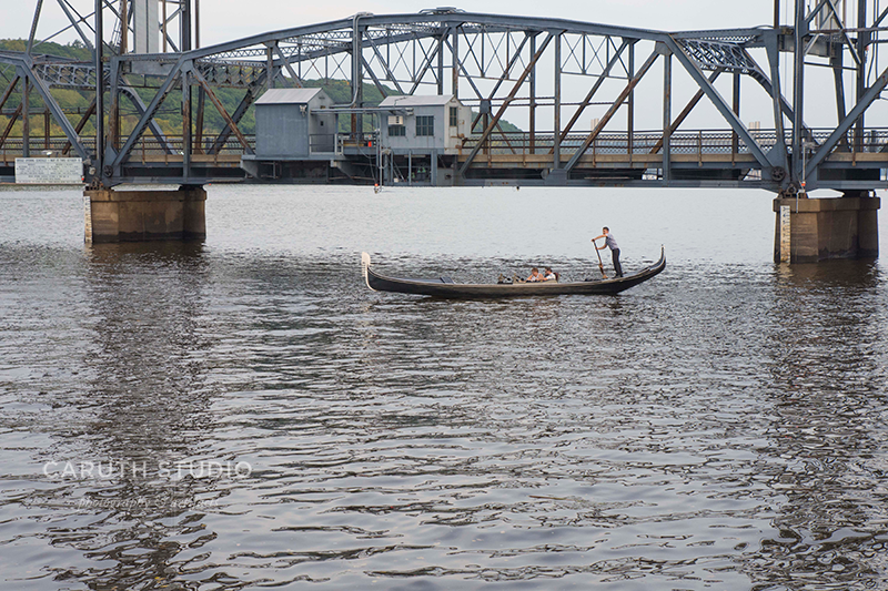 gondola being stirred by a boatman in black and white stripped shirt coasting in front of the lift bridge