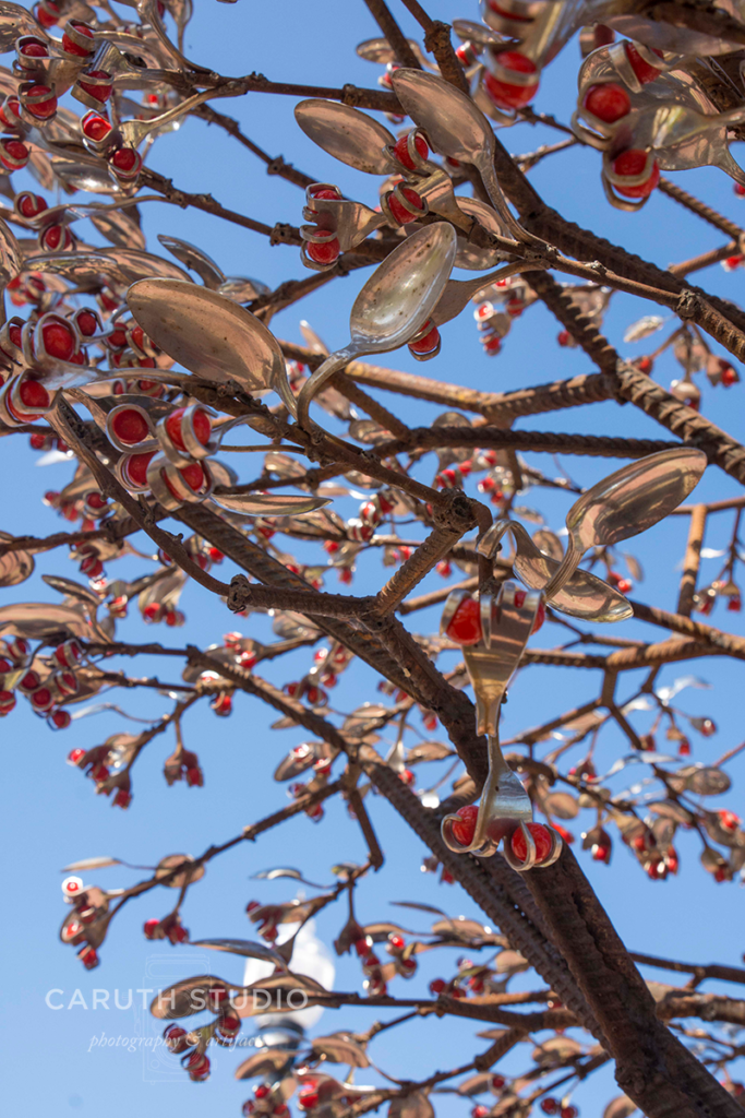 close up shot of the spoon leaves and red beads and metal branches