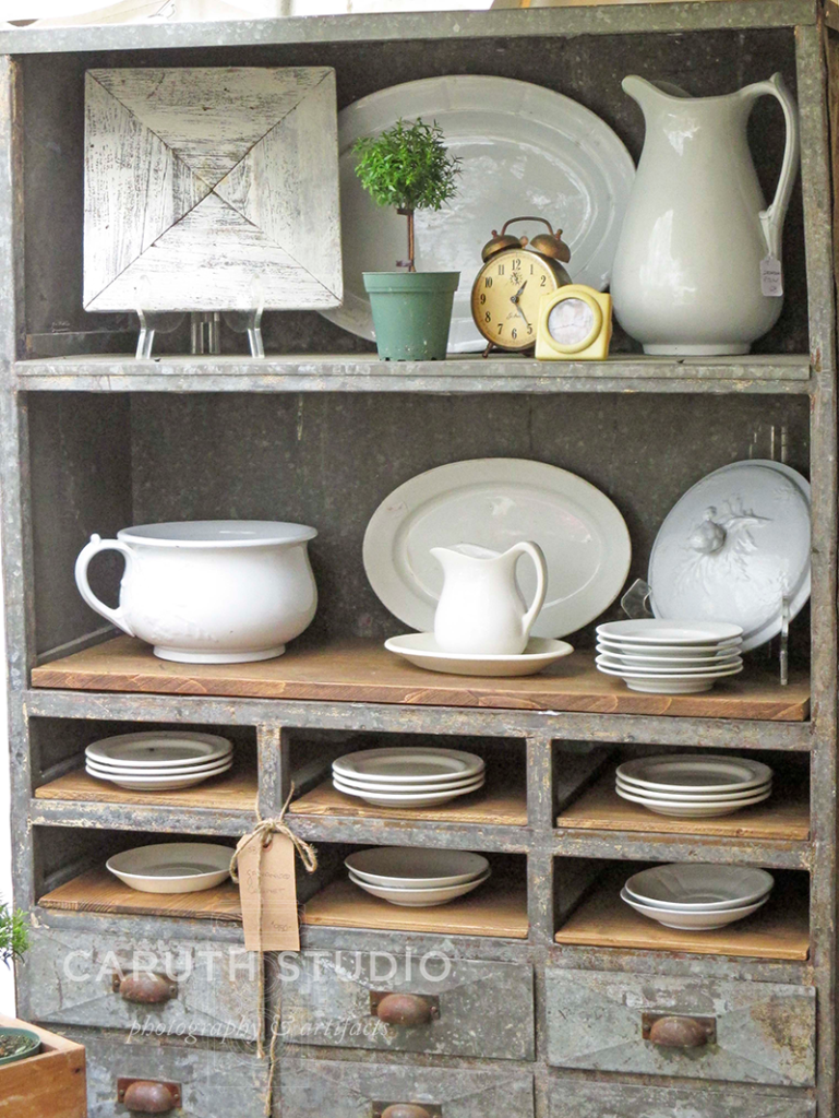 Vintage ironstone dishes with white glazing displayed in a zinc cabinet