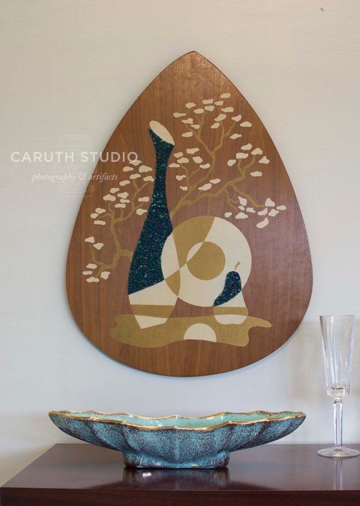 Close up of cabinet top where a boomerang dish sits in front of a guitar pick shaped art piece hung on the wall
