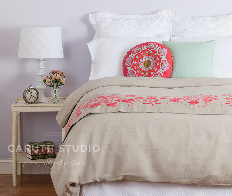 white, kaki, pink and mint bedding with coordinating bedside table with clear lamp with white shade, small flower vase and big ben alarm clock