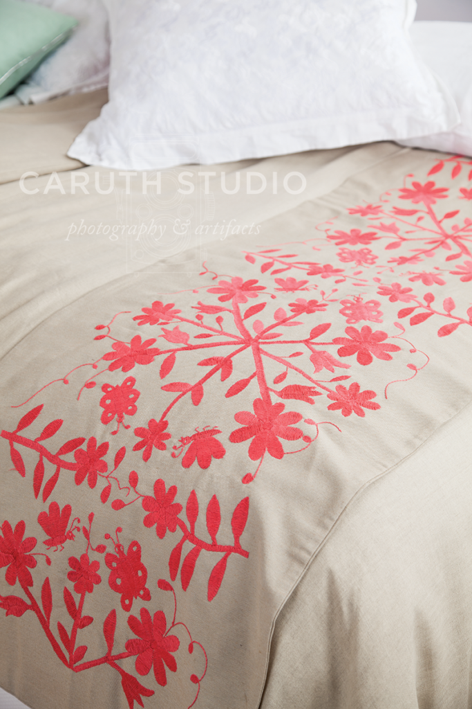 graphic pink floral pattern running along the length of the kaki bed runner laying across the foot of the bed
