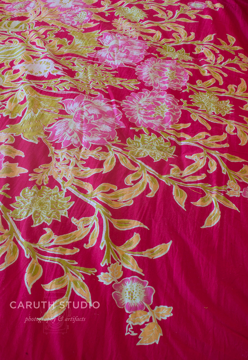 detail of pink bedspread with embroidered floral design
