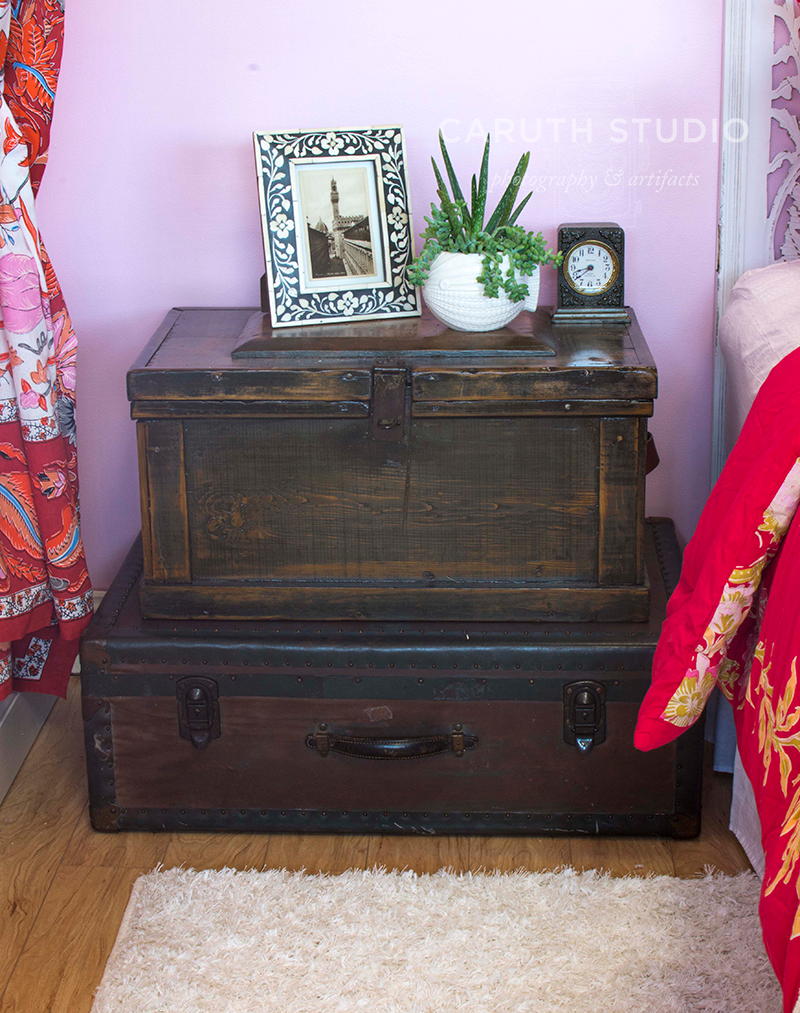 dark leather suitcase and wooden chest act as a bedside table