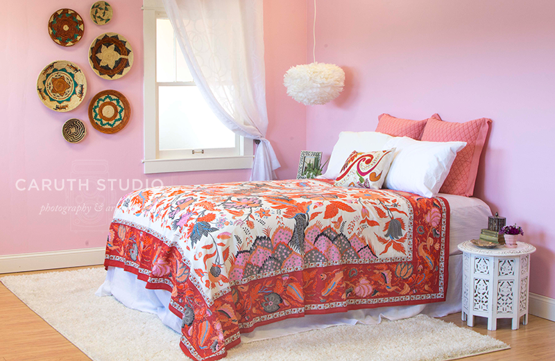 Boho bedroom with pink walls, jewel tone bedspread and basketry hanging on the wall
