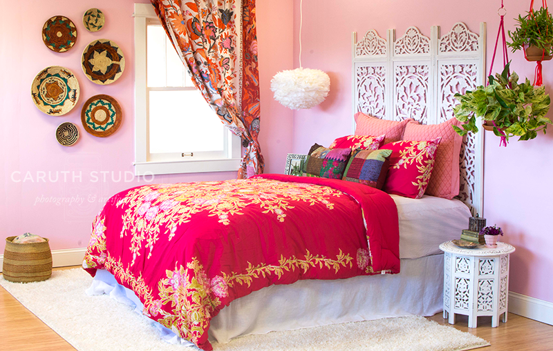 boho bedroom with pink bedspread with scroll detailing in white and gold