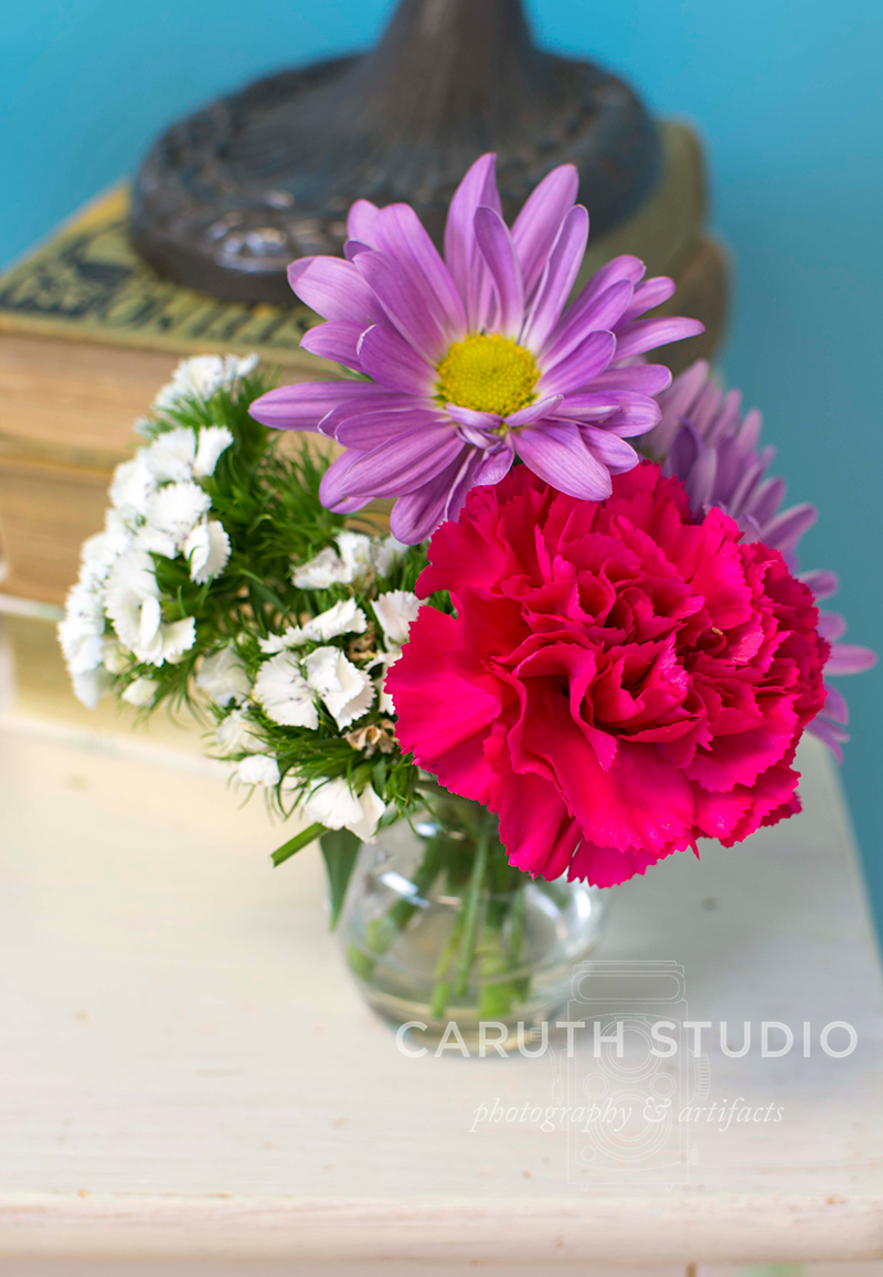 cut flowers in a vase on top of the nightstand