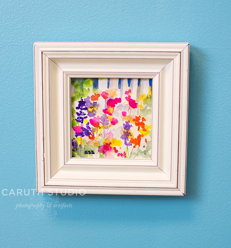 framed floral watercolor hanging on the wall above the nightstand