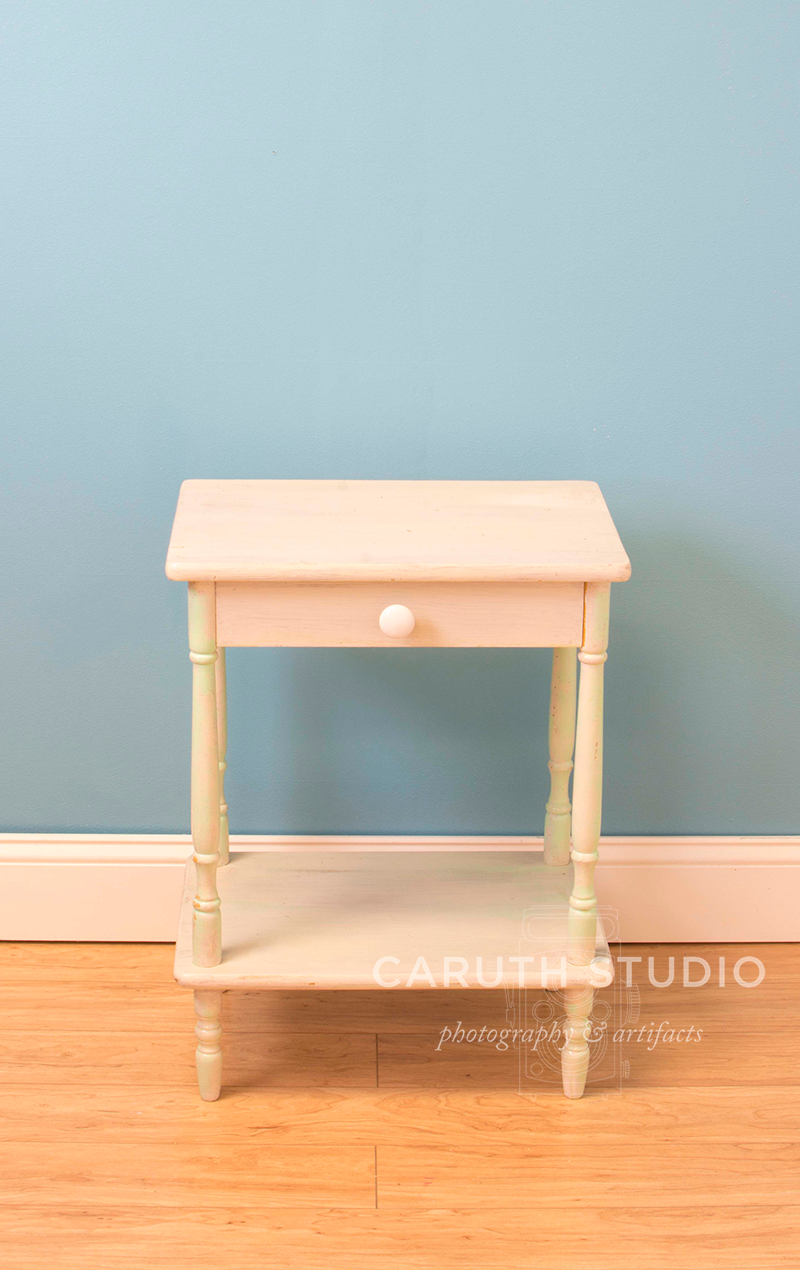 plain white cottage style nightstand in front of a blank blue wall