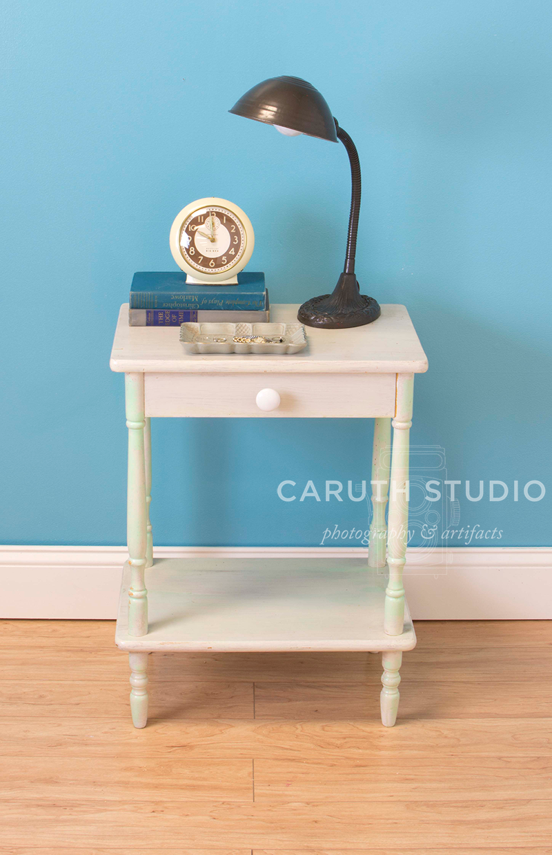 nightstand with a jewelry tray, lamp and clock which is now on a short stack of books