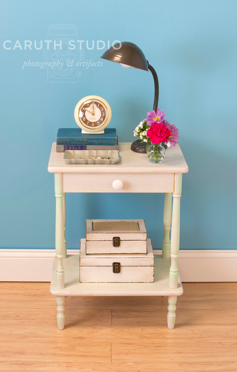 nightstand with clock on books, a lamp, jewelry tray, a vase of flowers on the top and stacked boxes on the bottom shelf