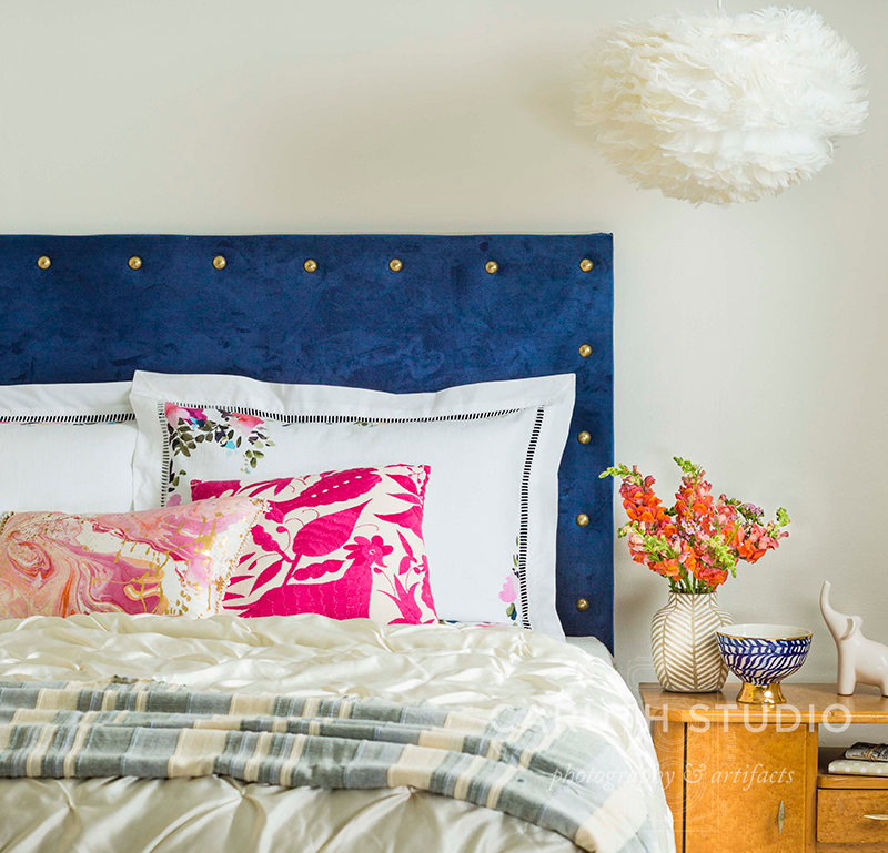 Upholstered headboard under a feathered pendant lamp