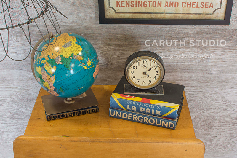 vintage desk nightstand top with detail of vintage globe and clock with stack of books on which the clock sits
