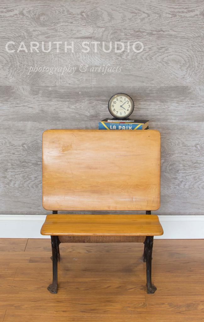 vintage wooden desk with a stack of books and clock