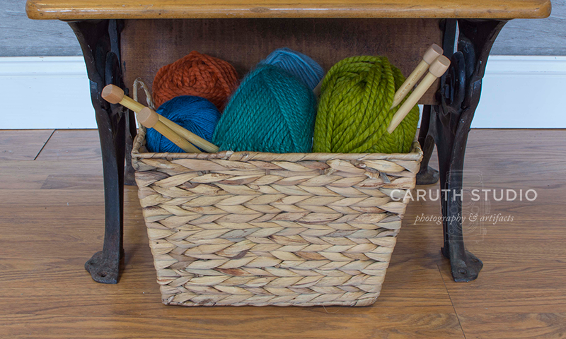 woven basket filled with yarn and knitting needles