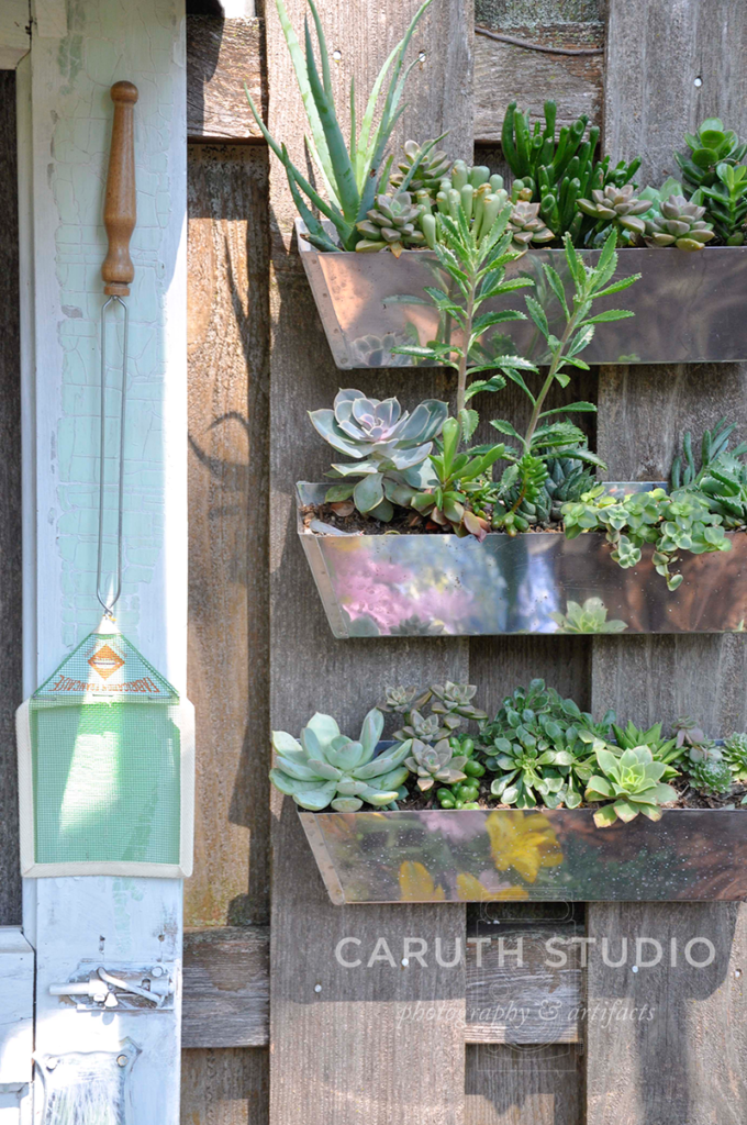 storage tins hung from fence behind vintage door potting bench