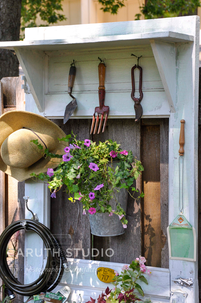 door potting bench with hanging flowers and hat