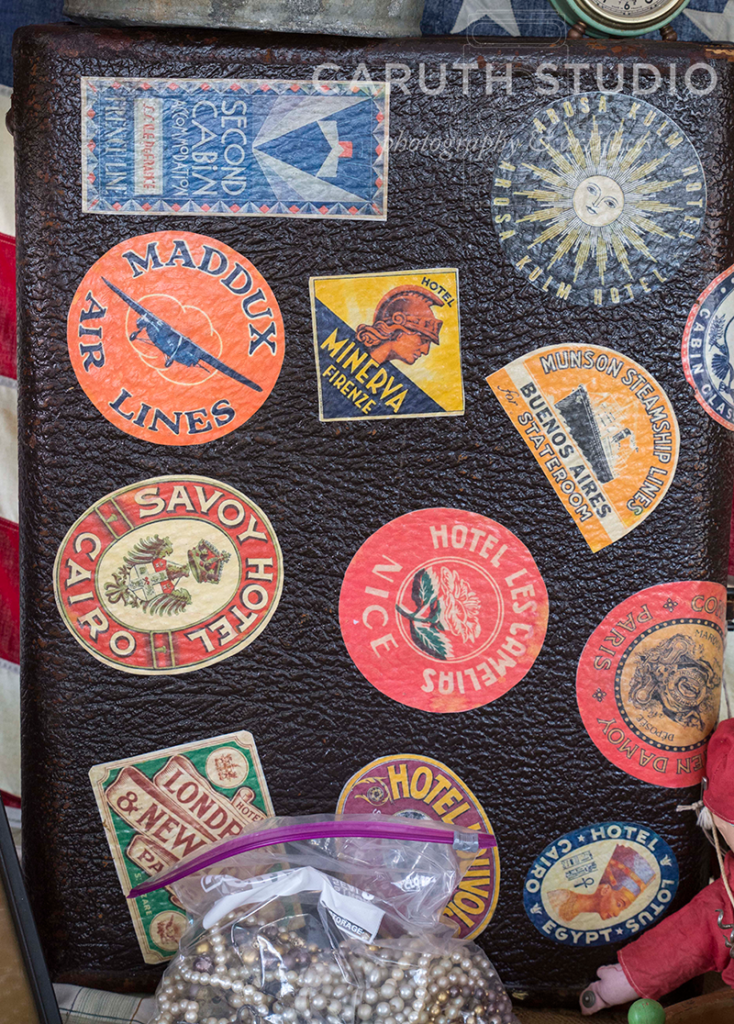 travel stickers on a black suitcase