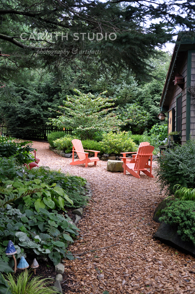Adirondack chairs in pine mulch patio surrounded by green plants