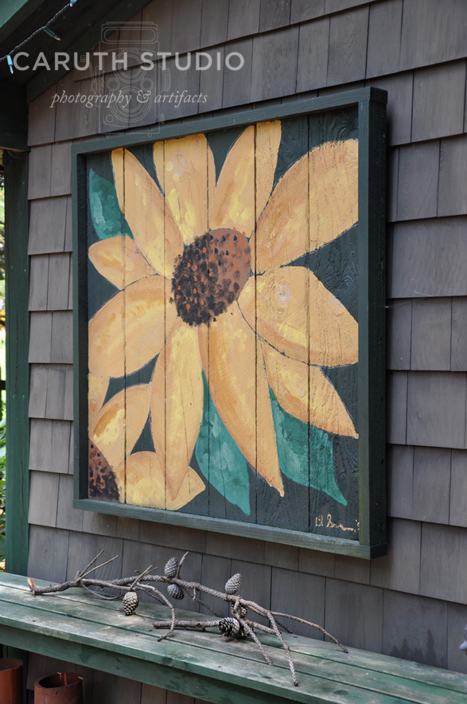 Framed sunflower hanging on outdoor wall