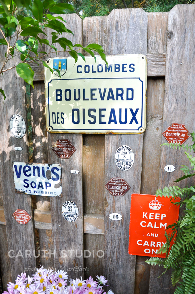 collections of garden signs hanging on a fence