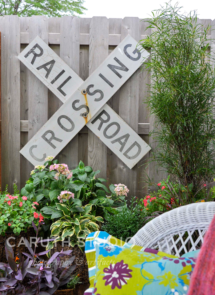 rail road crossing sign hung on a fence above potted garden and patio