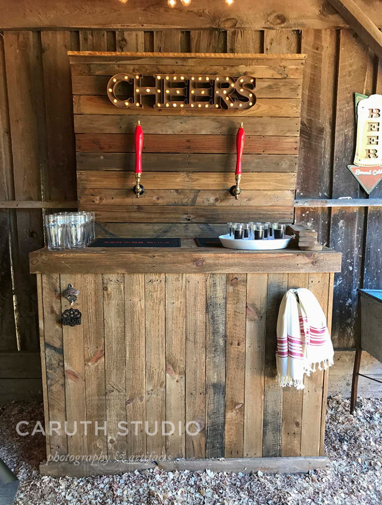 outdoor pallet bar with two beer taps and a lighted Cheers sign