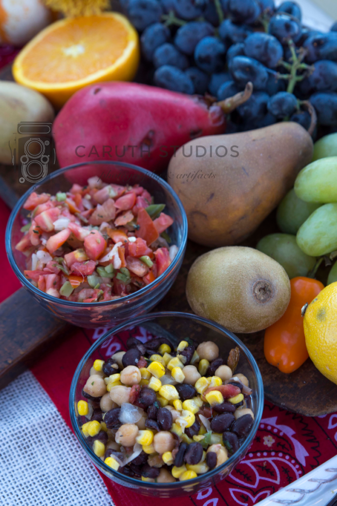 bowls of tomato and corn salsas amongst fruit and flowers